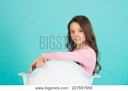 Small Girl Pose In White Armchair On Blue Background. Kid With Serious Face And Long Brunette Hair.
