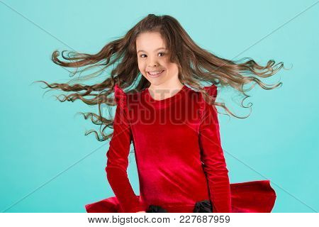 Small Girl Smile With Flying Hair On Blue Background, Fashion. Child Smiling With Long Brunette Hair