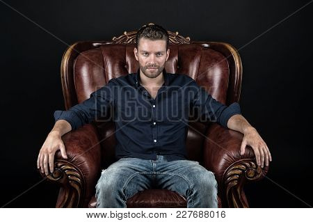 Guy Sit In Brown Armchair On Dark Background. Barber Salon, Barbershop. Fashion, Style Concept, Vint