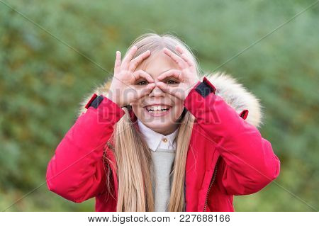 Small Girl Make Glasses With Fingers, Happiness, Childhood. Child Smile Outdoor, Autumn, Spring. Fas