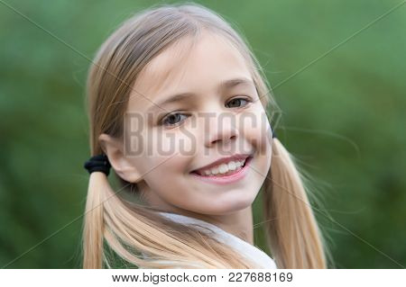 Little Girl Smile On Natural Background, Childhood. Child With Blond Hair Ponytails Smiling Outdoor.
