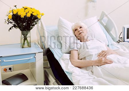 What To Go Home. Sad Retired Lady Looking Into Vacancy While Lying In A Hospital Bed And Undergoing