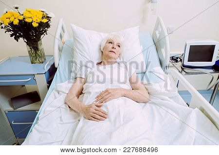 Depressing Thoughts. Pensive Retired Lady Lying In Her Hospital Bed And Looking Into Vacancy While T
