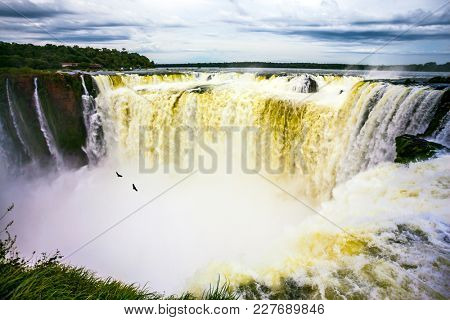 Grandiose waterfalls Iguazu in the rainy season. The most full-flowing waterfall in the world on the Parana River is the Garganta del Diablo. Concept of active, photographic and ecological tourism