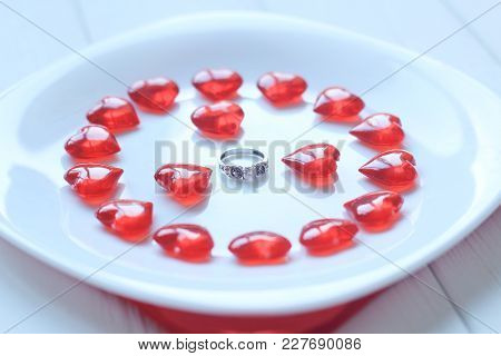 Close Up.ring And Red Hearts On A White Plate.holidays And Events