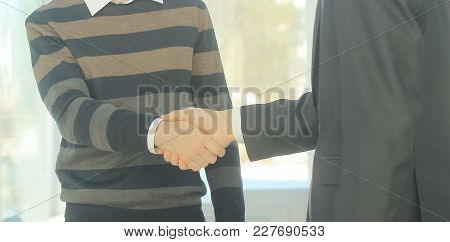 Closeup .the Financial Partners Shaking Hands Over A Desk.business Concept