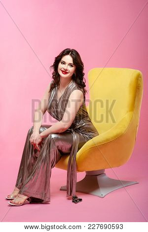Portrait Of Brunette Pretty Attractive Young Woman In Silver Disco Overalls Sitting In Yellow Stylis