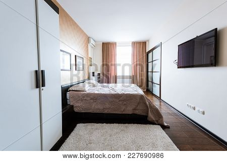 Close Up View Of Arranged Stylish Bedroom With Closet And Bed