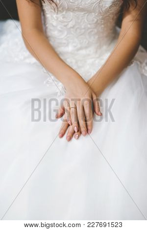 Bride Hands On Wedding Dress With Wedding Ring
