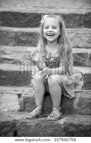 Small Happy Baby Girl Or Cute Child With Adorable Smiling Face And Bow In Blonde Hair In Blue Dress