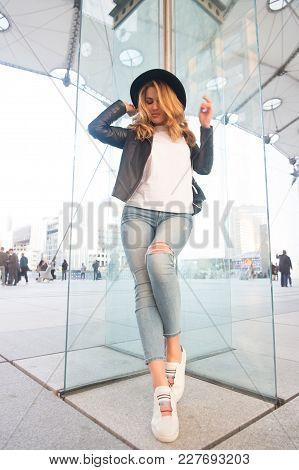 Girl In Hat, Jacket, Jeans, Sneakers Stand On Glass Wall In La Defense, Paris. Fashion, Beauty, Styl