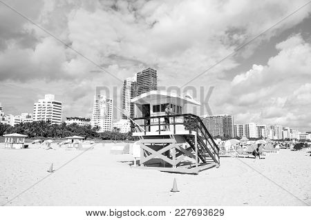 Miami, Usa - January 10, 2016: Man Or Male Lifeguard Patrolling Beach On Wooden Tower On Sunny Day W