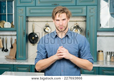 Man With Serious Face, Blond Hair In Blue Shirt Stand With Folded Fingers In Kitchen. Food Preparati