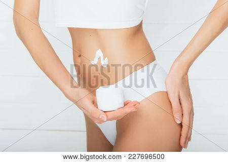 Woman Dressed In White Underwear Holding Anti Cellulite Cream To The Belly And Body, Close-up. Conce