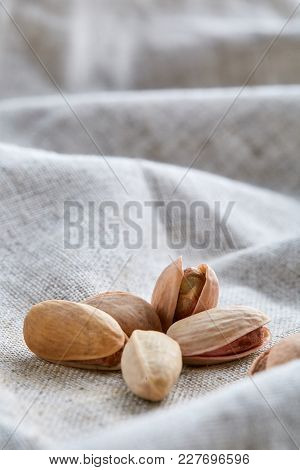 Top View Close-up Picture Of Pistachios On Light Grey Fabric Cotton Napkin, Shallow Depth Of Field,