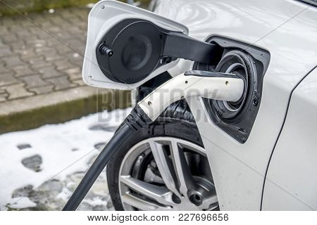 View Of An Electric Car Charging And In The Background A Blurred View Of A Car
