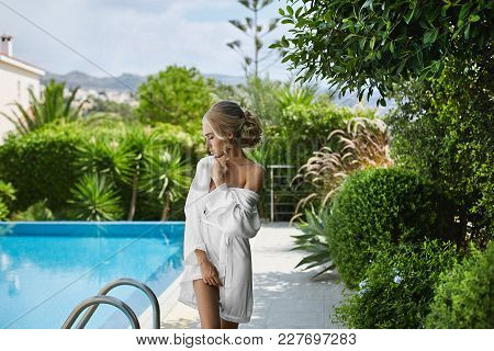 Beautiful, Sexy And Hot Blonde Model Girl In Peignoir Posing Half Naked Near Swimming Pool.