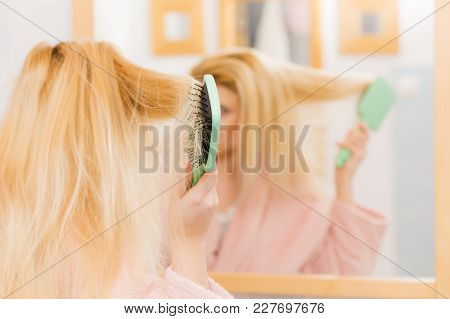 Woman Wearing Dressing Gown Brushing Her Long Blonde Hair, Morning Beauty Routine. Haircare And Hair