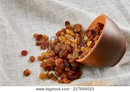 Close-up Picture Of Ceramic Clay Bowl With Golden Raisins On Light Grey Tablecloth Or Napkin, Copy S