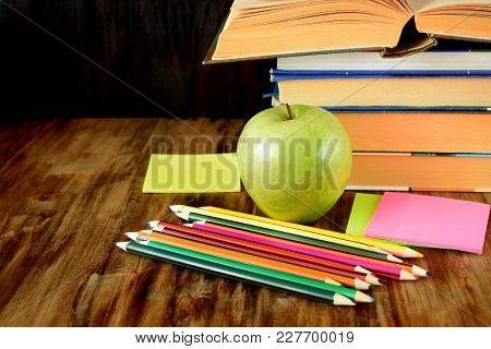 Group Of Coloured Pencils, Green Apple, Stickers And A Pile Of Books On A Wooden Table
