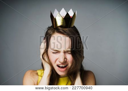 Discontented Young Girl Covered Her Ears, Her Head Was Crowned With A Golden Crown