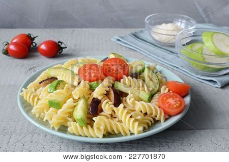 Fusilli Pasta With Tomatos And Grilled Zucchini, Eggplant. Vegeterian Lunch On Grey Wooden Backgroun