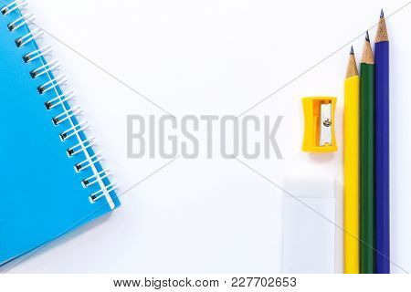 Pencil-sharpener, Eraser, Notebook And Pencil Isolated On White Table Background. With Copy Space Fo