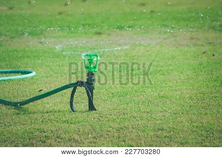 Lawn Water Sprinkler On Green Grass Spraying And Watering Meadow At Outdoor Garden In Summer Seasona