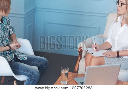 What Worries You The Most. Side View On A Female Professional And A Young Boy Sitting And Talking Wh