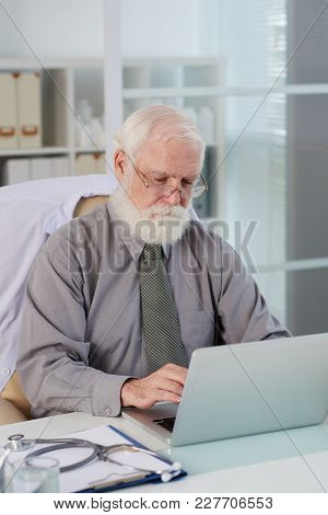 Aged Bearded General Practitioner Working On Laptop