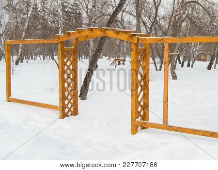 Wooden Arch In The Park In Winter, Cloudy Day And Snow.