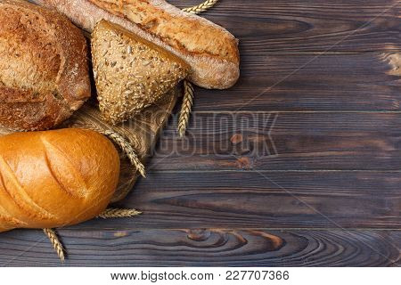 Homemade Loaf Of Wheat Bread Baked On Wooden Background. Top View With Copy Space.