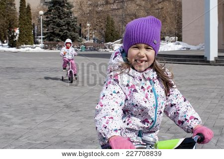 A Girl Is Smiling Happily On A Bicycle