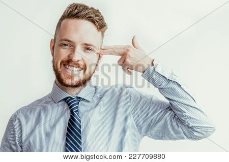 Closeup Portrait Of Smiling Young Business Man Looking At Camera And Shooting Himself In Head With F