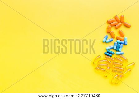 Color Capsules. Medicine Pills On Yellow Background Top View.