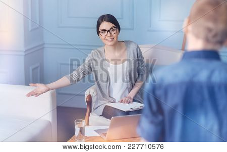 Please Feel At Home. Smiling Young Professional Sitting With A Clipboard On Her Knees And Proposing