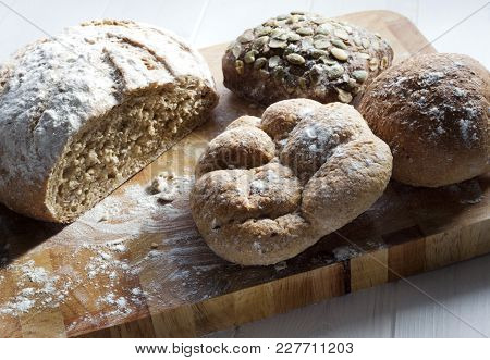Wholemeal Bread And Several Rolls On Chopping Board