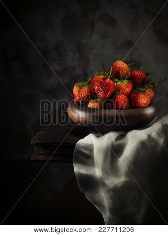 Strawberries In Wooden Cups Placed On White Cloth And Old Wooden Floor.