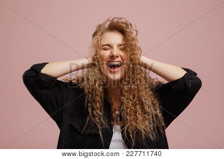 Cheerful Beautiful Girl With Curly Hair, Braces On Her Teeth, Laughs And Is Wide With Her Mouth Open