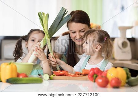 Mom And Kids Daughters Have A Fun Cooking In Family Home Kitchen.