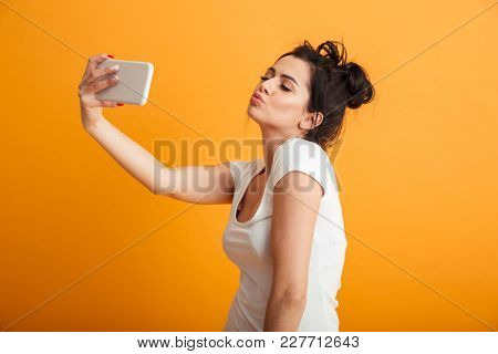 Image of amazing young woman standing over yellow background wall. Looking aside make selfie by mobile phone blowing kisses.
