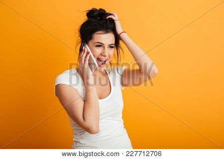 Image of happy young woman standing over yellow background wall. Looking aside talking by mobile phone.