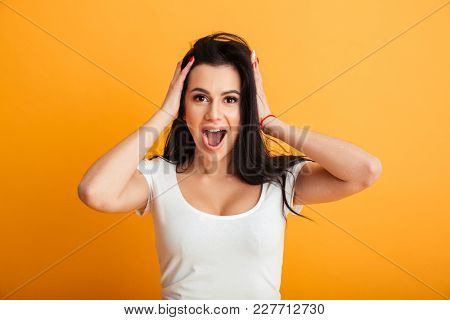 Photo of shocked young woman standing isolated over yellow background wall. Looking camera.