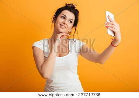 Image of cheerful young woman standing over yellow background wall. Looking aside make selfie by mobile phone.