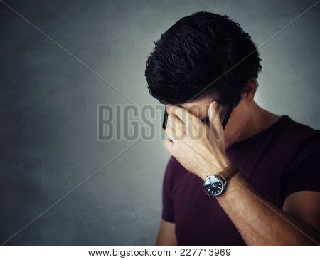 Young Man Covering His Face Looking Down