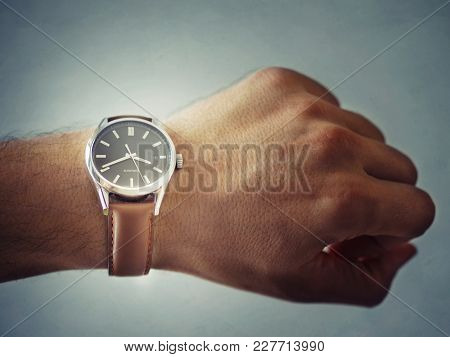Classic Watch With A Brown Leather Strap And A Black Dial Worn On A Hand.