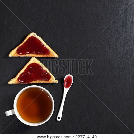 Slice Of Toasted Bread With Delicious Jam And A Cup Of Tea On Black Stone Background, Top View With