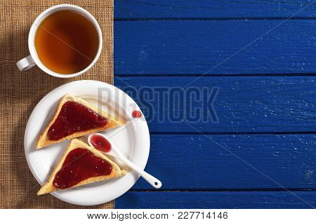 Slice Of Toasted Bread With Homemade Jam In Plate And A Cup Of Tea For Breakfast On The Blue Wooden