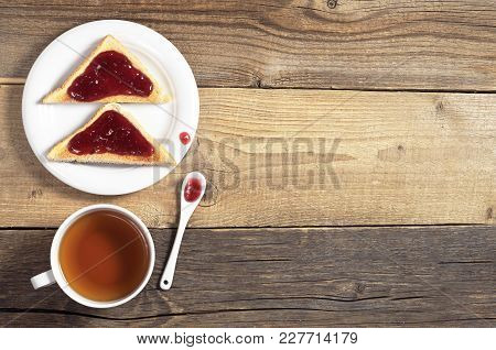 Cup Of Tea And Toasted Bread With Delicious Jam In Plate On The Old Wooden Table, Top View With Spac