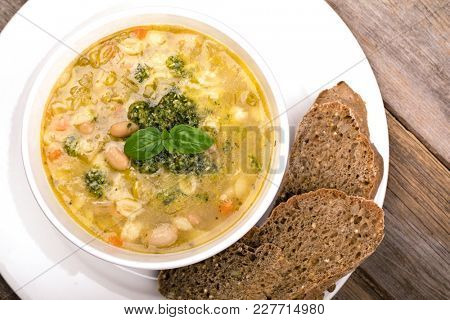Fresh minestrone soup, made with mixed vegetables, white cannelini beans and pasta shells, topped with fresh pesto, basil oil and a sprig of fresh basil. Served with seeded brown bread. Top view.